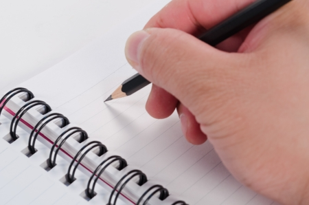 hand writing with pencil on notebook photo