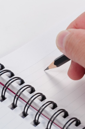hand writing with pencil on notebook Stock Photo - 14215488