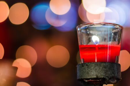 Fortune candle in glass cup with bokeh background photo