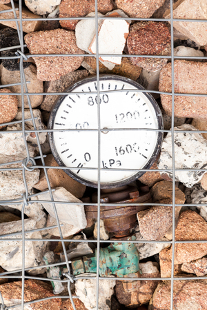 gabion mesh: Old historic pressure gauge embedded into the rock of a gabion retaining wall Stock Photo