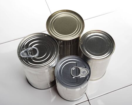 ring pull: four silver food cans, one can on its side show the ring pull on the lid
