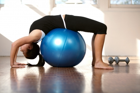 Young caucasian woman on stretched over a fitness ball photo