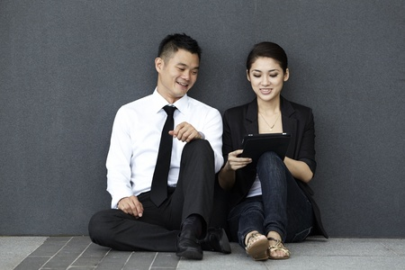 Two business people using a touch pad Stock Photo - 10320621