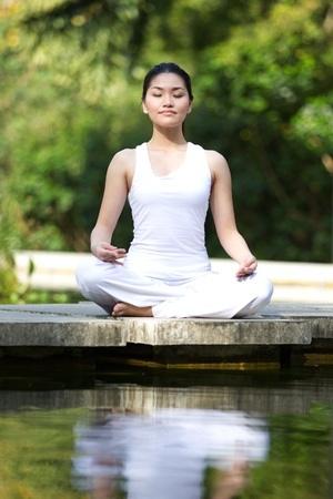 natural pool: Woman in white Performing yoga in natural setting