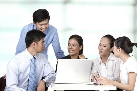 laptop asian: Colegas asi�ticos de negocios que trabajan en torno a un ordenador port�til