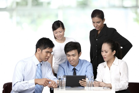 southeast asian ethnicity: Asian business colleagues working around a Digital Tablet