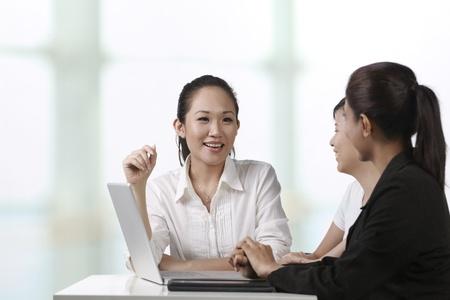laptop asian: Colegas de negocios asi�ticos trabajan alrededor de un ordenador port�til