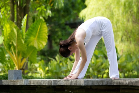 poses: Donna in bianco yoga Performing in ambiente naturale