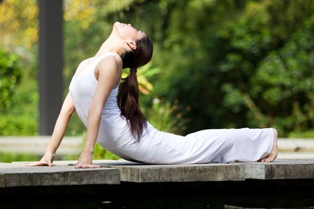 yoga  pose: Woman in white Performing yoga in natural setting