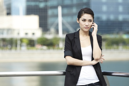 front office: Business woman using a Phone in modern urban setting
