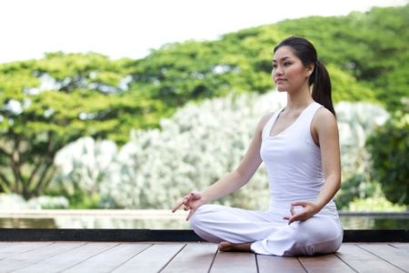lifestyle outdoors: Woman in white Performing yoga in natural setting