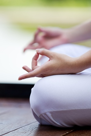 female pose: Woman in white Performing yoga in natural setting