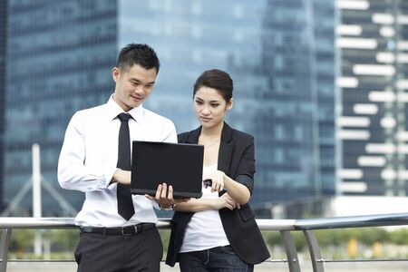 asian youth: Business man and woman using a Laptop in modern urban setting
