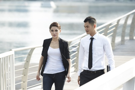 casal: Business Man and Woman walking in modern urban setting