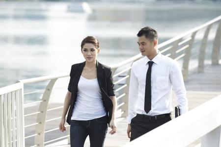 Business Man and Woman walking in modern urban setting photo