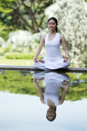 asian trees: Woman in white Performing yoga in natural setting