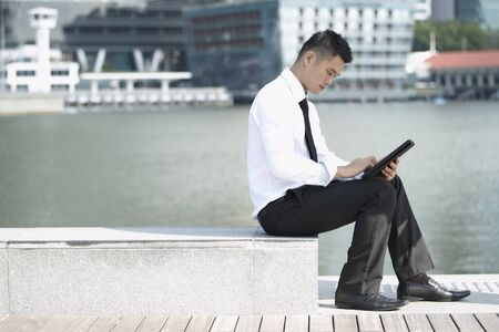 Business man using a touch pad Stock Photo - 10322469
