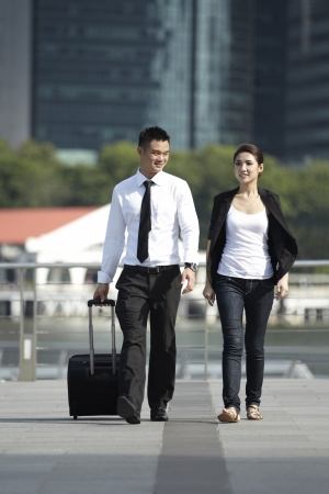 Business man and Business woman Walking with a wheeled Suitcase photo