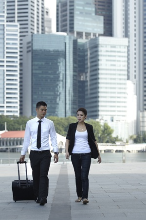 wheeled: Business man and Business woman Walking with a wheeled Suitcase