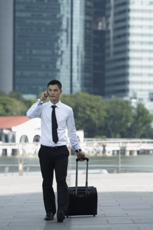 businesswear: Business man Walking with a wheeled Suitcase on phone