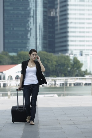 Business woman Walking with a wheeled Suitcase on phone Stock Photo - 10322522