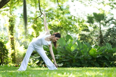 natural setting: Woman in white Performing yoga in natural setting
