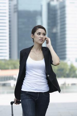 Business-Frau zu Fuß mit einem Rollkoffer am Telefon Standard-Bild - 10322527