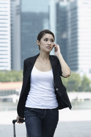 businesswear: Business woman Walking with a wheeled Suitcase on phone Stock Photo