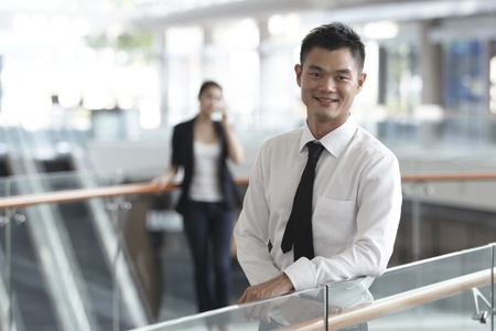 asian office lady: Asian Business man with colleague in background