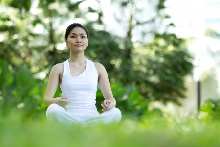 yoga outside: Woman in white Performing yoga in natural setting