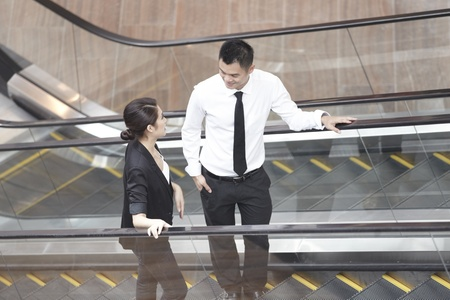 Asian Business man and woman talking on an Escalator photo