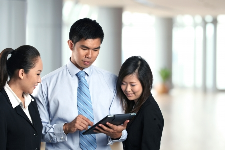 Three Asian business people looking at the screen of Digital Tablet photo