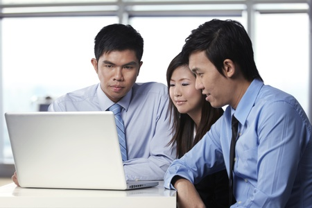 Asian business colleagues working around a laptop Stock Photo - 10322520