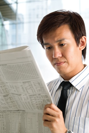 Businessman reading the business section of a newspaper. photo