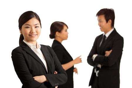 Business woman with colleagues at the back out of focus Stock Photo - 10336531