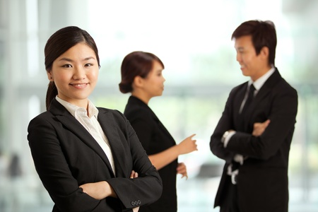 Business woman with colleagues at the back out of focus Stock Photo - 10336533