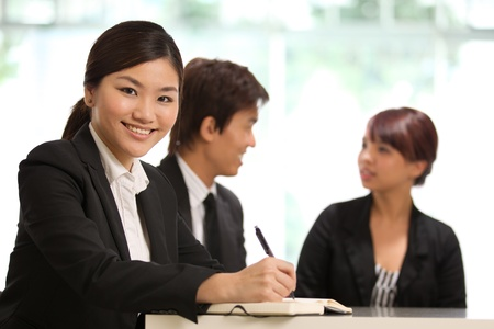 Business woman with colleagues at the back out of focus Stock Photo - 10336663