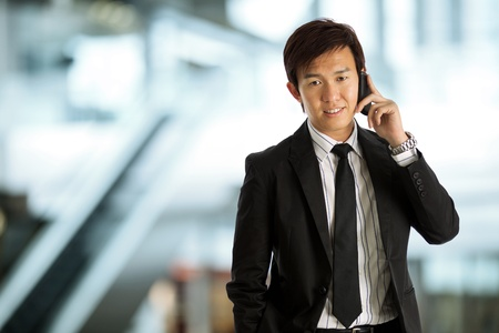 asian businessman: Business exective in corporate setting on phone