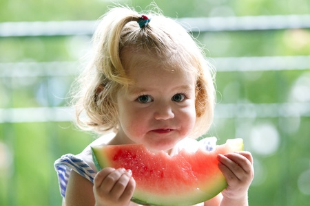 upper half: Young girl eating watermelon
