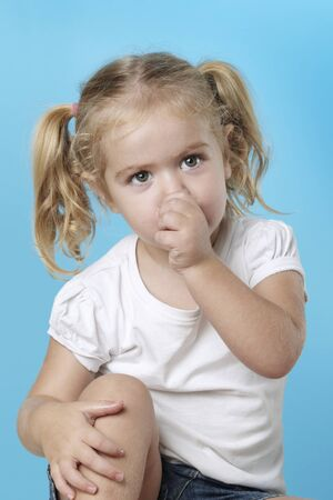 A young caucasian child sucking her thumb.