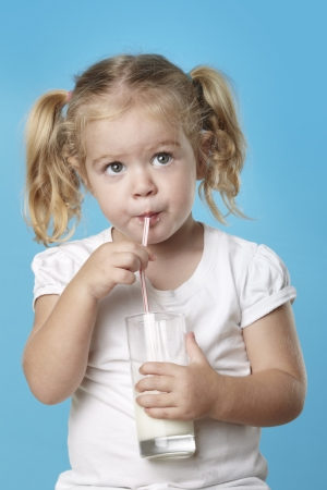 Young caucasian girl drinking a glass of milk. Stock Photo - 10443060