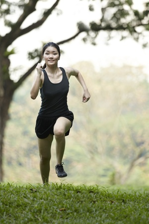 Picture of a woman running through the park. photo