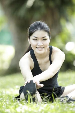 Asian female runner stretching before exercising.  photo