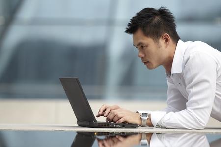 usando computadora: El hombre asi�tico con su port�til puertas