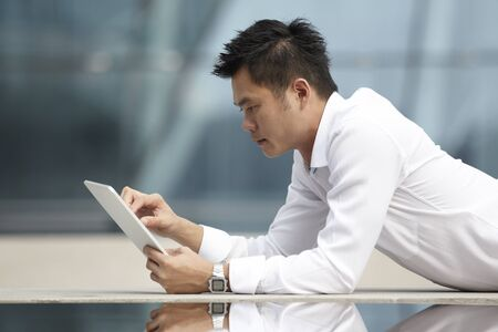 asian business man: Asian Business man using a  touch pad PC