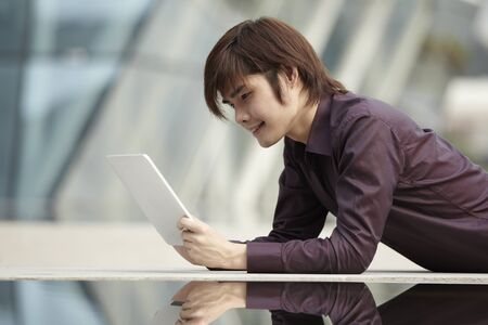 Asian Business man using a  touch pad PC photo
