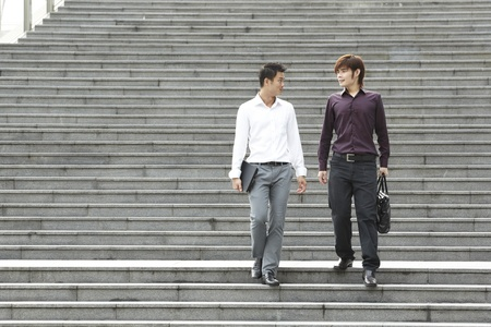 Two Asian Business men walking on stairs photo