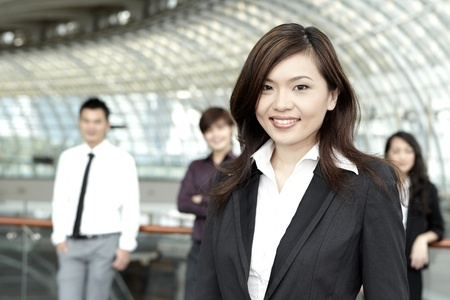 asian office lady: Asian Business woman with colleagues in the background out of focus