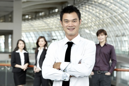 Asian Business man with colleagues in the background out of focus photo