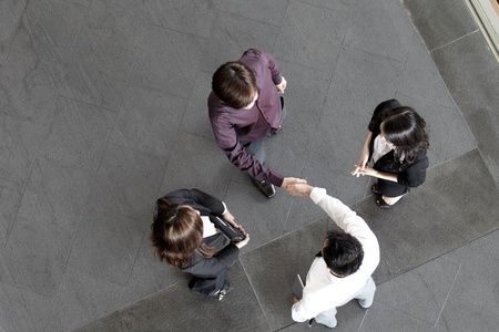 employment: High angle view of Asian Business people shaking hands.  Stock Photo